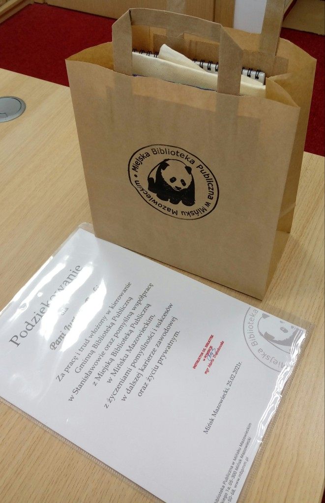 zdjęcie przedstawia podziękowanie dla pani Justyny oraz okolicznościowy upominek w torebce z logo Miejskiej Biblioteki Publicznej w Mińsku Mazowieckim